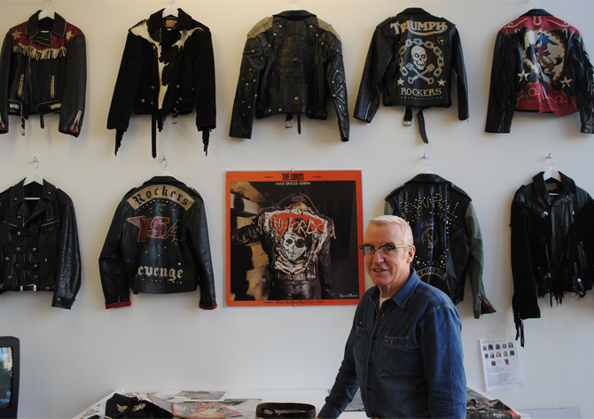 Lloyd Johnson, standing in front of his 'leather jackets from the 90s' wall