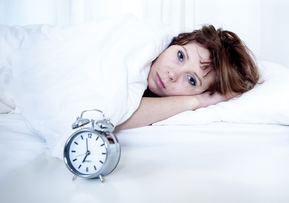 woman insomnia sleeping disorder with alarm clock in bed